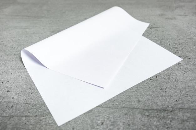 Foglio di carta bianco su sfondo grigio. vista del primo piano di libro bianco piegato che pone sul piano d'appoggio stilizzato del cemento