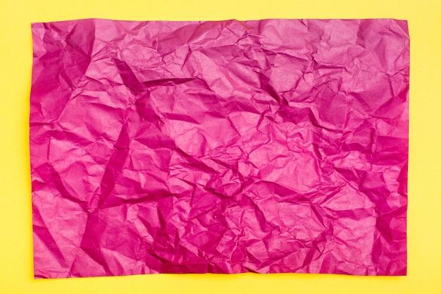 Foglio di carta colorato sgualcito in bianco porpora su un fondo giallo del cartone. sfondo eterogeneo materico. vista dall'alto. copia spazio