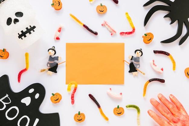 Foglio di carta con decorazioni di halloween e caramelle con mano insanguinata