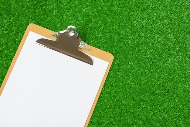 Foglio di carta e attrezzature sportive su erba