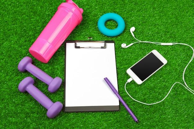Foglio di carta e attrezzature sportive sul primo piano dell'erba