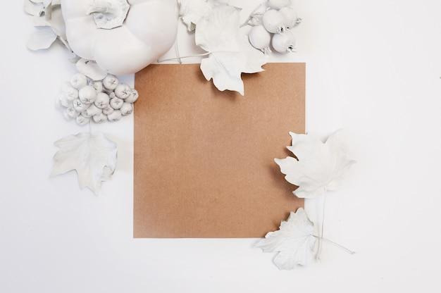 Foglio di carta kraft, zucca bianca, bacche e foglie su uno sfondo bianco.