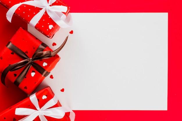 Foglio di carta vicino a regali per san valentino