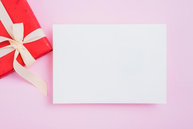 Foglio di carta vicino alla scatola di san valentino sul rosa