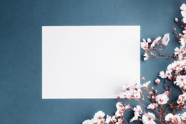 Foglio di carta vuoto circondato da piccoli fiori bianchi. scheda in bianco su sfondo blu