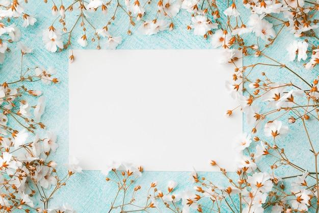 Foglio di carta vuoto circondato da piccoli fiori bianchi.