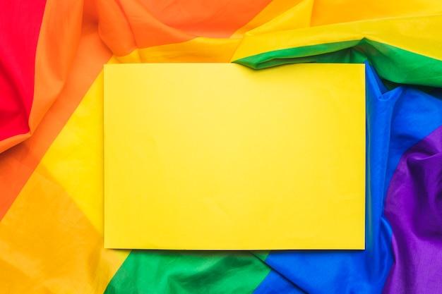 Foglio di carta vuoto giallo sulla bandiera lgbt stropicciata