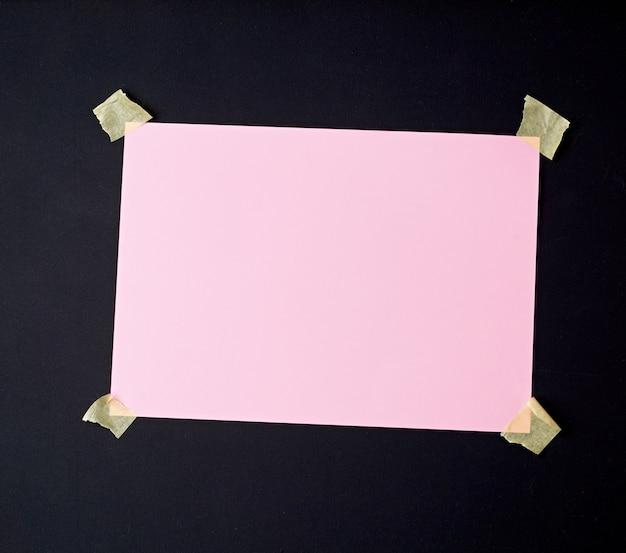 Foglio rosa bianco attaccato con nastro adesivo a una superficie di legno nera