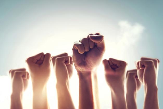 Folla di manifestanti. la gente alzò il pugno in aria combattendo per i propri diritti con effetto luce solare. concetto di rivoluzione o protesta.