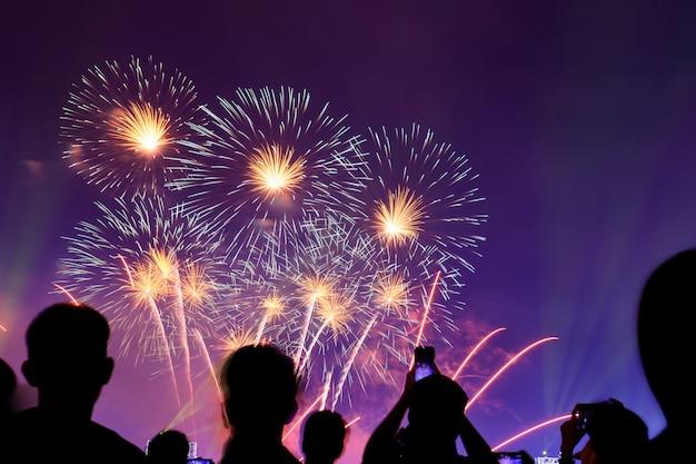 Folla guardando fuochi d'artificio e celebrando la città fondata. i bei fuochi d'artificio variopinti visualizzano nell'ambiente urbano per la celebrazione sulla notte scura.