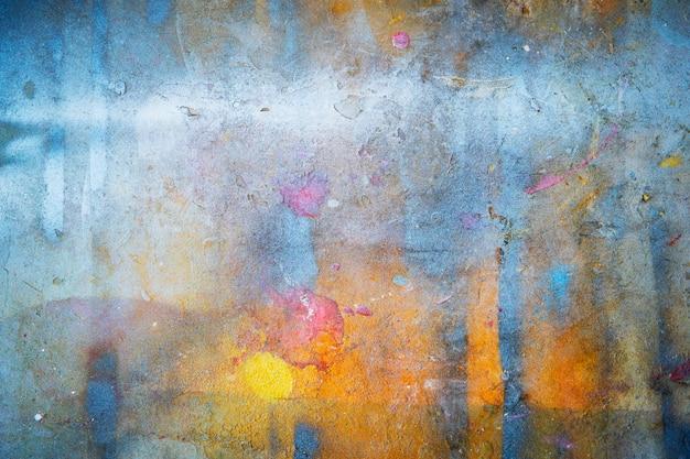 Fondo astratto da variopinto dipinto sulla parete con il lerciume e graffiato.