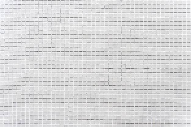 Fondo astratto dalle mattonelle di mosaico decorate dei mattoni grigi sulla parete.