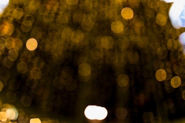 Fondo astratto dell'oro con effetto della luce morbido del bokeh della sfuocatura