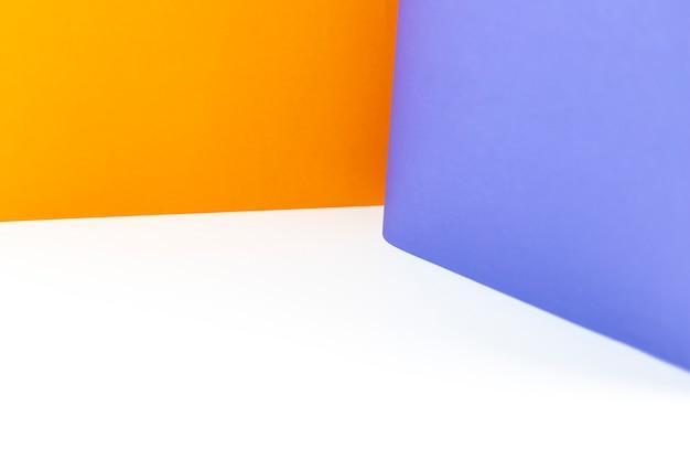 Fondo astratto delle carte di colore arancio e porpora sulla tavola bianca.
