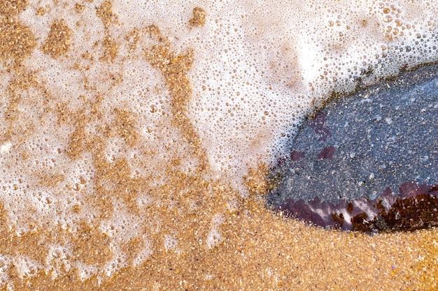 Fondo bagnato strutturato della spiaggia di sabbia