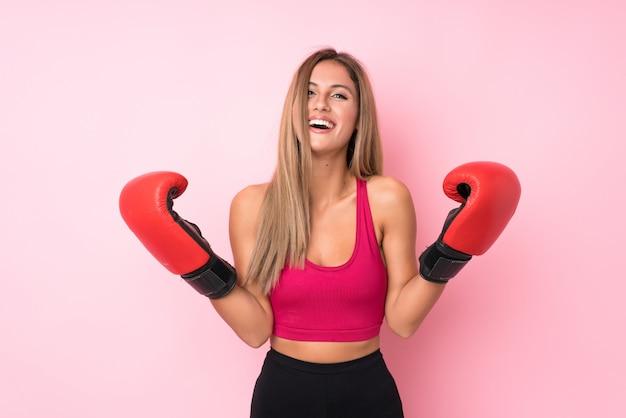 Fondo biondo della donna di giovane sport con i guantoni da pugile