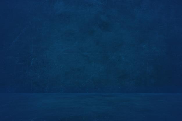 Fondo blu scuro della parete del cemento, showroom vuoto per presentare prodotto