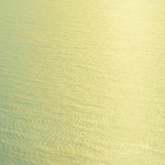 Fondo d'annata dell'acqua di mare con luce del sunflare dal sole