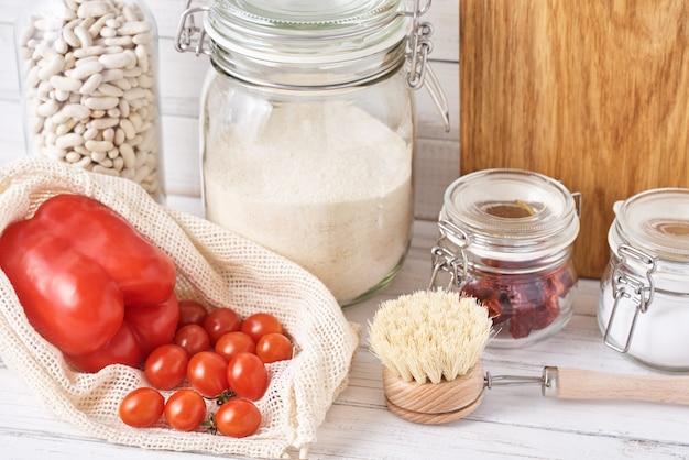 Fondo degli utensili della cucina con il tagliere e contenitori di vetro riutilizzabili con ingredienti alimentari. concetto di rifiuti zero