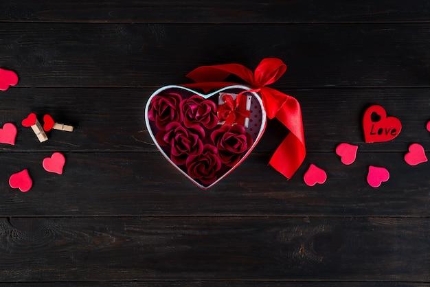 Fondo dei biglietti di s. valentino con mini regalo e rosa in scatola del cuore