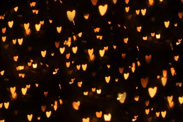 Fondo del bokeh del cuore, concetto di san valentino di amore. cuori su sfondo nero