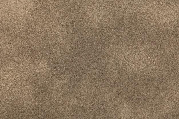Fondo del primo piano leggero del tessuto della pelle scamosciata del bronzo.