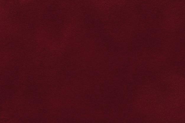 Fondo del tessuto rosso scuro del velluto, primo piano