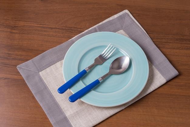 Fondo dell'alimento con il piatto, il cucchiaio, la forchetta e il tovagliolo vuoti, disposizione piana.