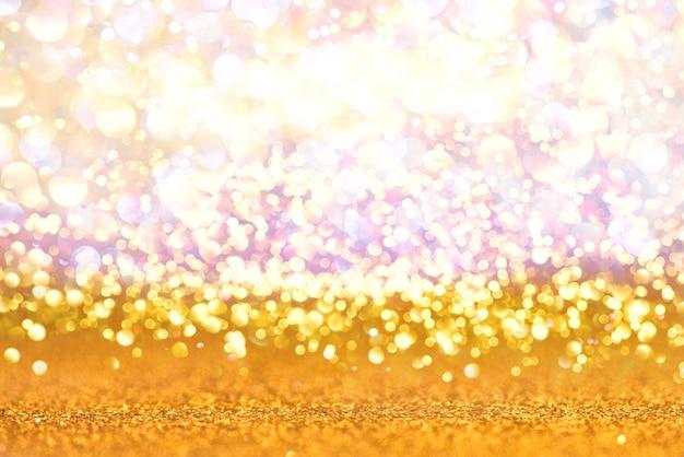Fondo dell'estratto del bokeh di struttura delle luci di scintillio dell'oro defocused