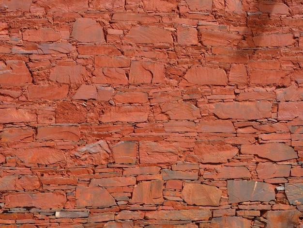 Fondo della parete di pietra e fondo dell'argilla rossa