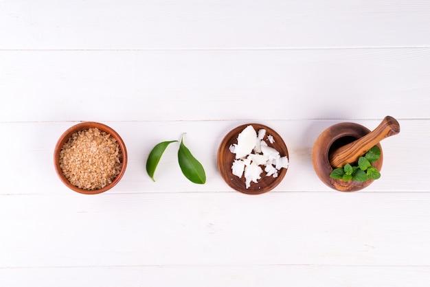 Fondo della stazione termale con i prodotti cosmetici naturali fatti a mano della preparazione su legno bianco