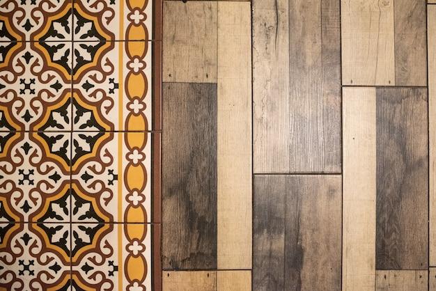 Fondo delle mattonelle mediterranee di retro colori accanto al pavimento di legno.