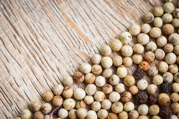 Fondo delle spezie, fine su delle erbe e spezie pepe mescola i grani di pepe rossi e bianchi neri o la vista superiore del seme di pepe