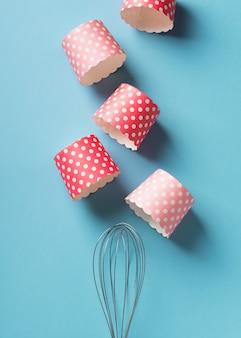 Fondo di cottura con forme di torta rosa su sfondo blu