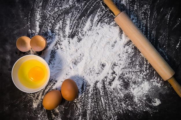 Fondo di cottura con il mattarello con farina. sul tavolo scuro