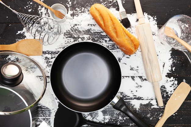 Fondo di cottura con pane, farina, matterello, padella, cucchiai di legno su legno nero