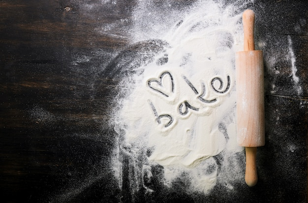 Fondo di cottura cuore di farina, testo cook e mattarello sul tavolo scuro