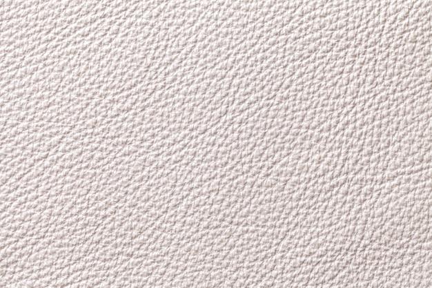 Fondo di cuoio beige bianco di struttura con il modello, primo piano.