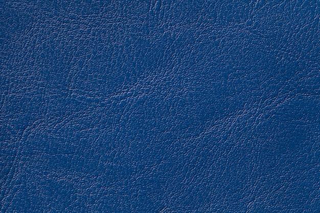 Fondo di cuoio scuro di struttura dei blu navy, primo piano. sfondo denim incrinato dalla pelle delle rughe