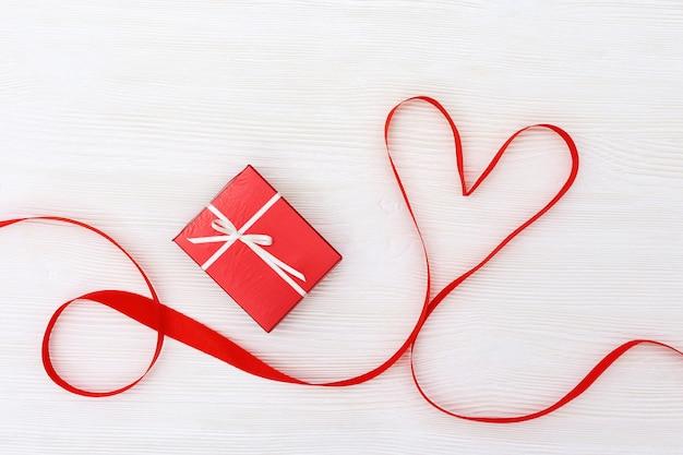 Fondo di festa con il regalo e cuore su legno bianco.