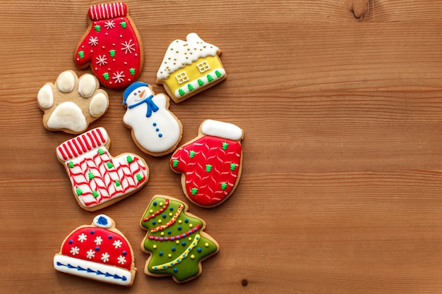 Fondo di festa del nuovo anno di natale, biscotti del pan di zenzero del colorfull e coni sulla tavola di legno. copia spazio. concetto di vacanza.