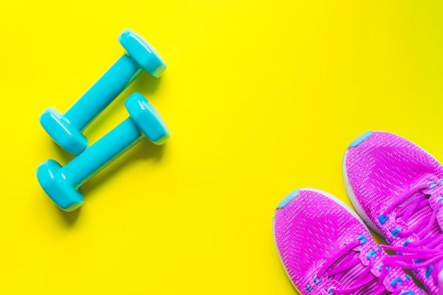 Fondo di forma fisica, attrezzatura per la palestra e testa di legno domestica e scarpe da tennis su giallo