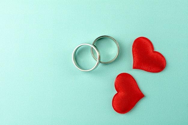 Fondo di giorno di biglietti di s. valentino con i cuori e la fede nuziale rossi su fondo blu