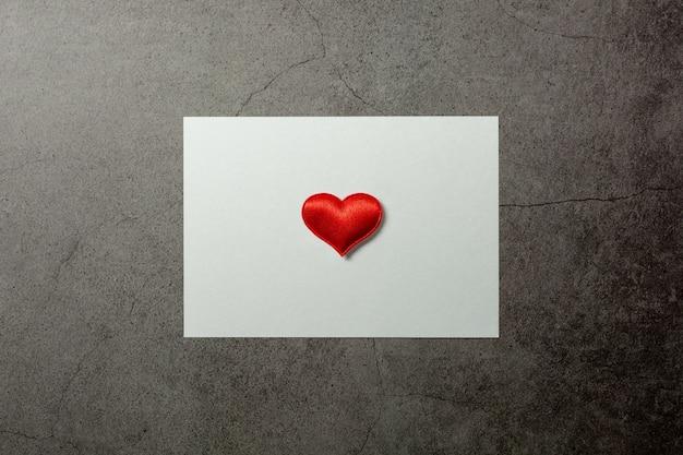 Fondo di giorno di biglietti di s. valentino con i cuori rossi e un libro bianco sulla vecchia tavola concreta