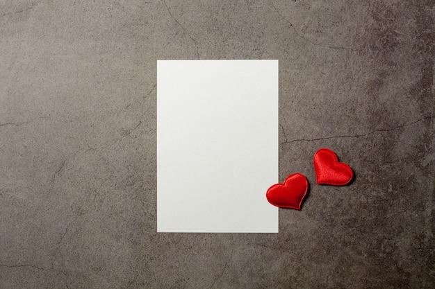 Fondo di giorno di biglietti di s. valentino con i cuori rossi e una carta in bianco sulla vecchia tavola concreta