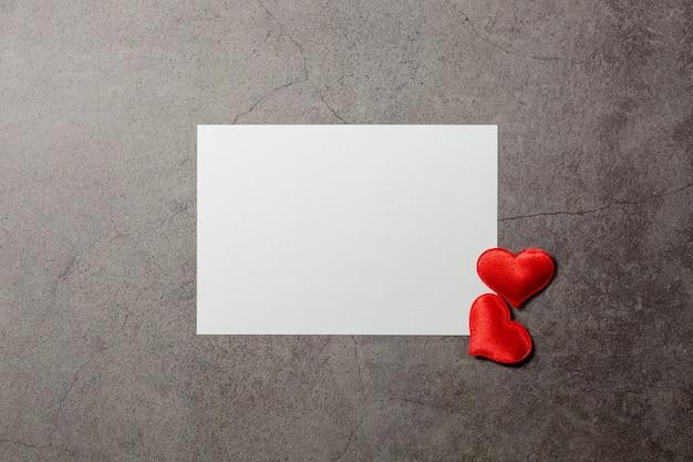 Fondo di giorno di biglietti di s. valentino con i cuori rossi e una carta in bianco sulla vecchia tavola concreta.