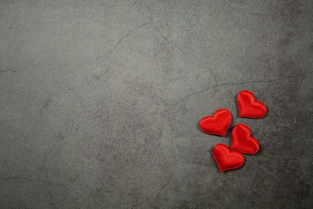 Fondo di giorno di biglietti di s. valentino con i cuori rossi sulla vecchia tavola concreta