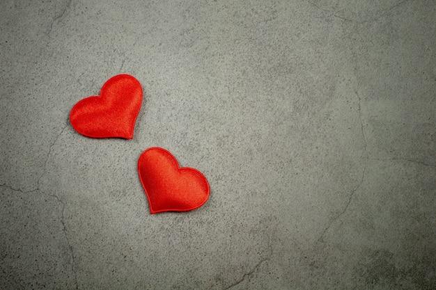 Fondo di giorno di biglietti di s. valentino con i cuori rossi sulla vecchia tavola concreta.