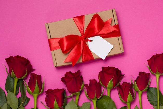 Fondo di giorno di biglietti di s. valentino, fondo rosa senza cuciture, rosa rossa, etichetta dell'arco del nastro del regalo