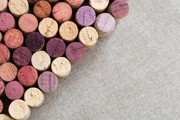 Fondo di legno con il primo piano del sughero delle bottiglie con vino rosso e bianco situato diagonalmente.